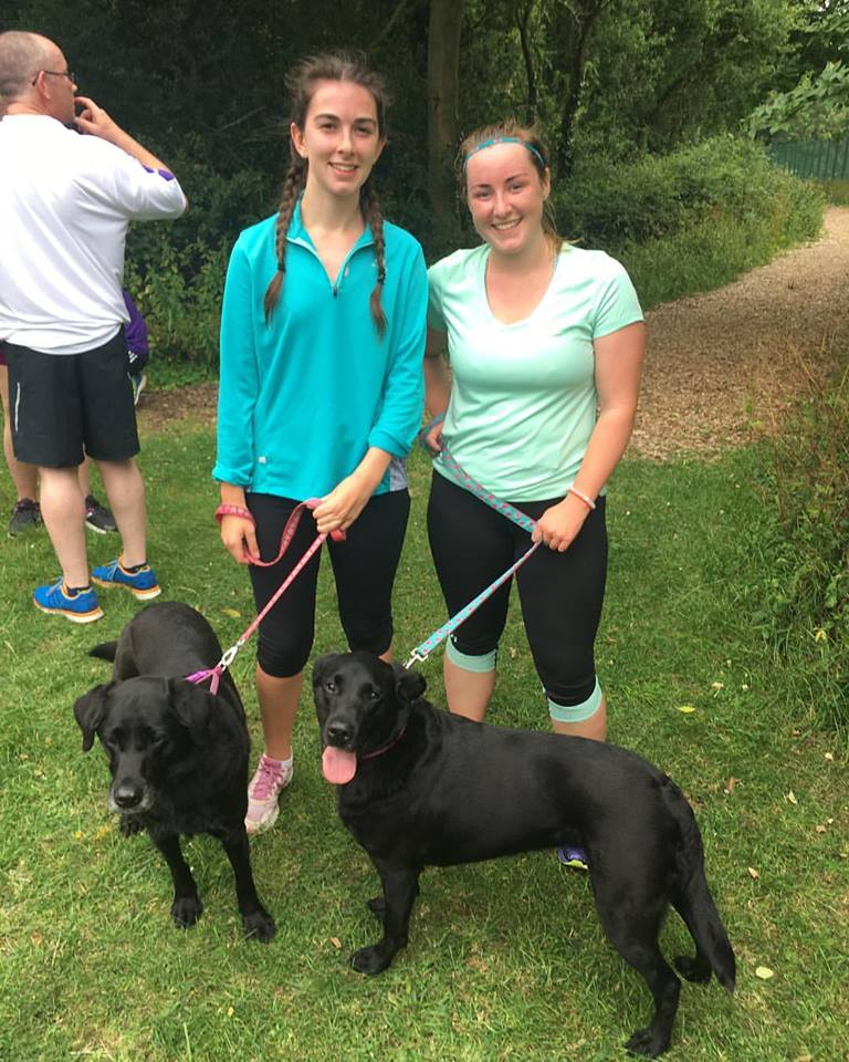 Two girls in running kit with two dogs