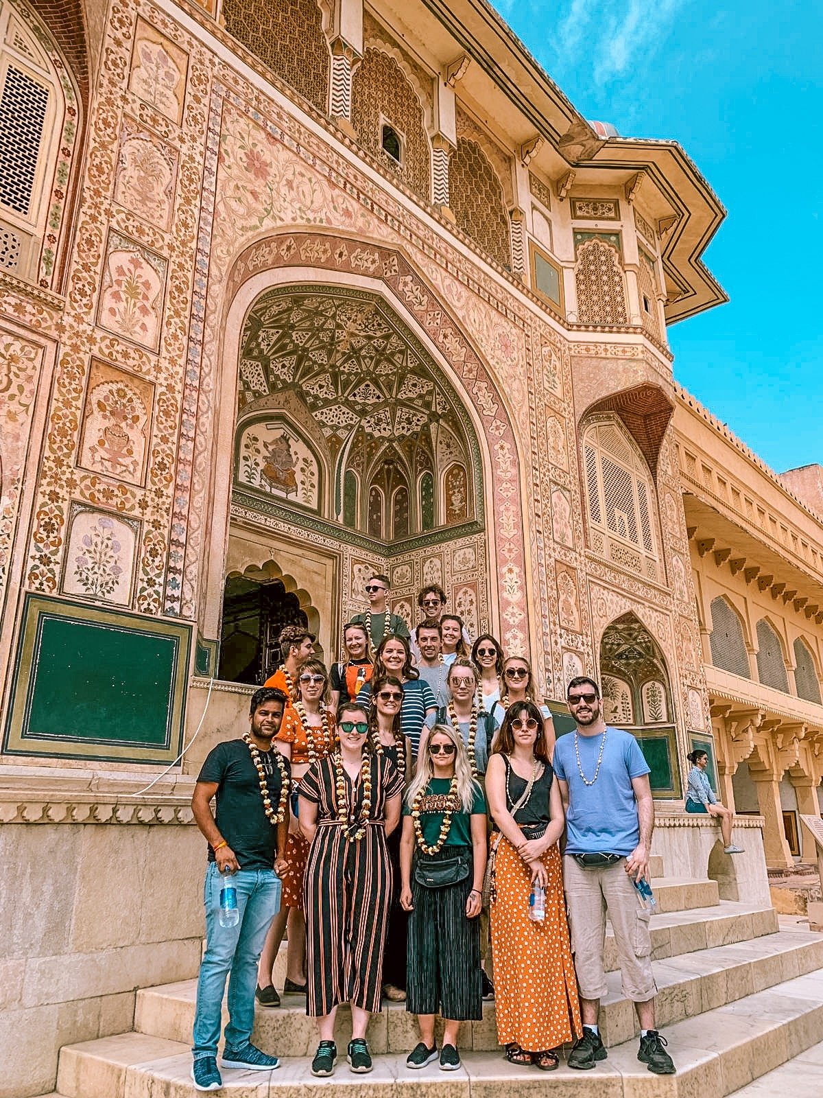 A group picture outside the beautiful mosaics of a fort