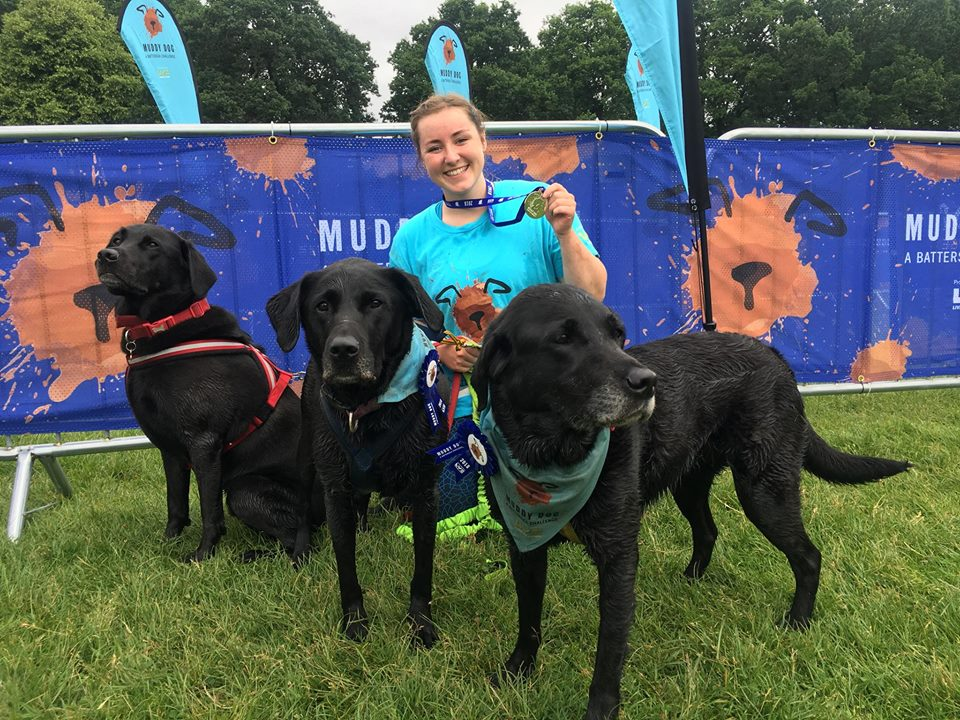 A girl with 3 dogs and a medal at a muddy obstacle race