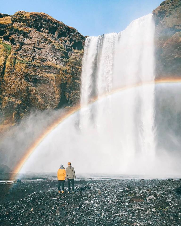 A couple holding hands at the bottom of a waterfall. There is a rainbow coming from the reflection.