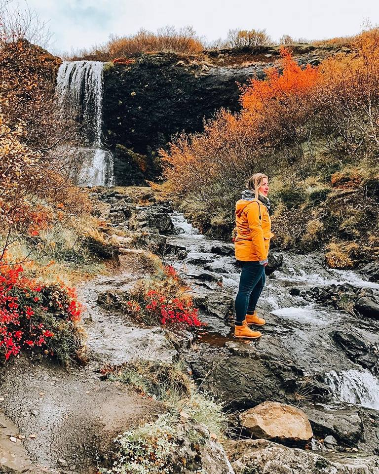 A flurry of reds, oranges and yellows at a hidden waterfall. A girl in yellow jacket is stood looking out.