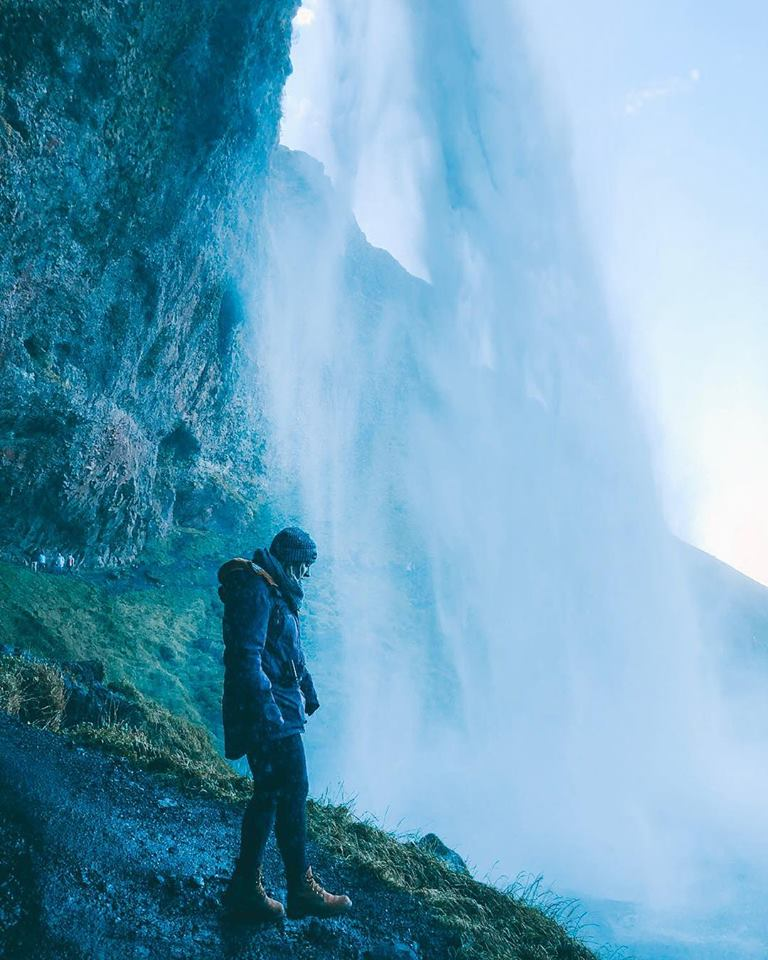 A girl in jacket standing underneath a giant waterfall.