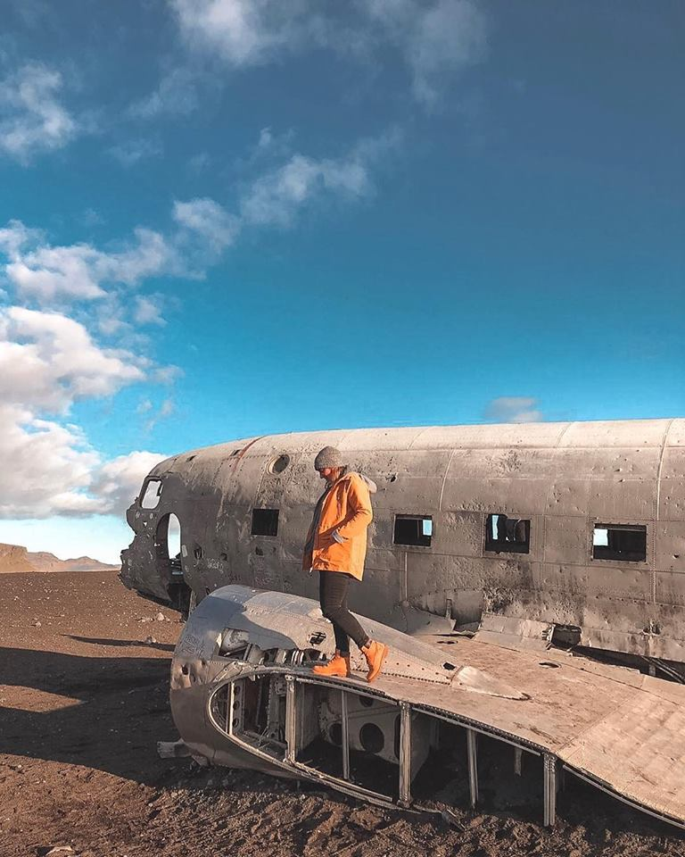 A girl stood on the wing of the famous Iceland plane.