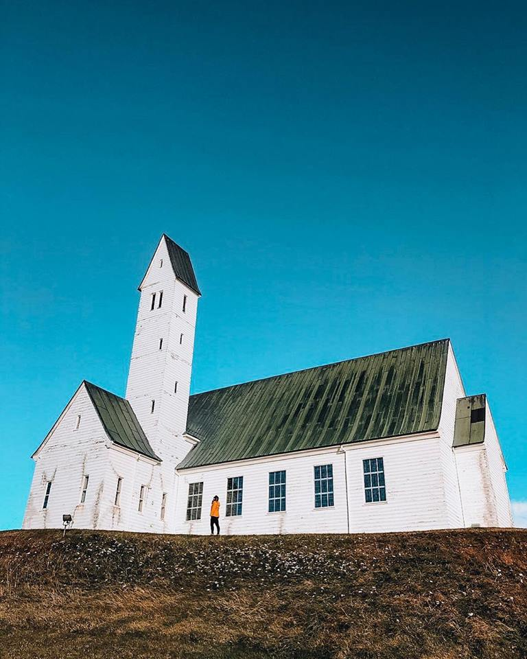 A girl is yellow jacket looking up at a Icelandic church. White church with green roof and blue skies