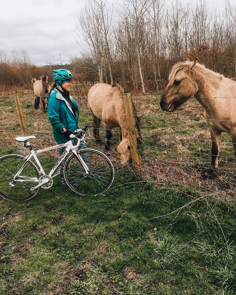 A girl with a bike next to some horses