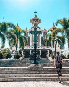 A girl walking up the stairs towards a very christian church with palm trees