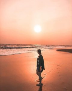 A very red looking sunset as a girl walks down an empty beach