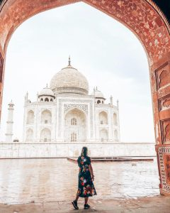A girl in a arch way looking at the Taj Mahal