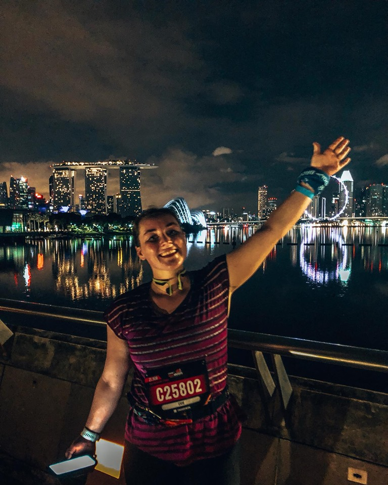 A girl stood in front of a lit up Singapore skyline at night