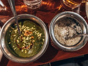 A very green korma with a bowl of rice next to it