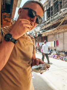Boy in sunglasses eating samosa with chilli/mint dip in a street