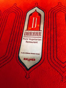 A red menu with Darbar pure vegetarian restaurant on the front