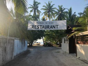 A sandy track with palm trees at the end, with a big banner saying restaurant