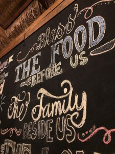 Lots of writing on a blackbord - bless the food before us and the family beside us