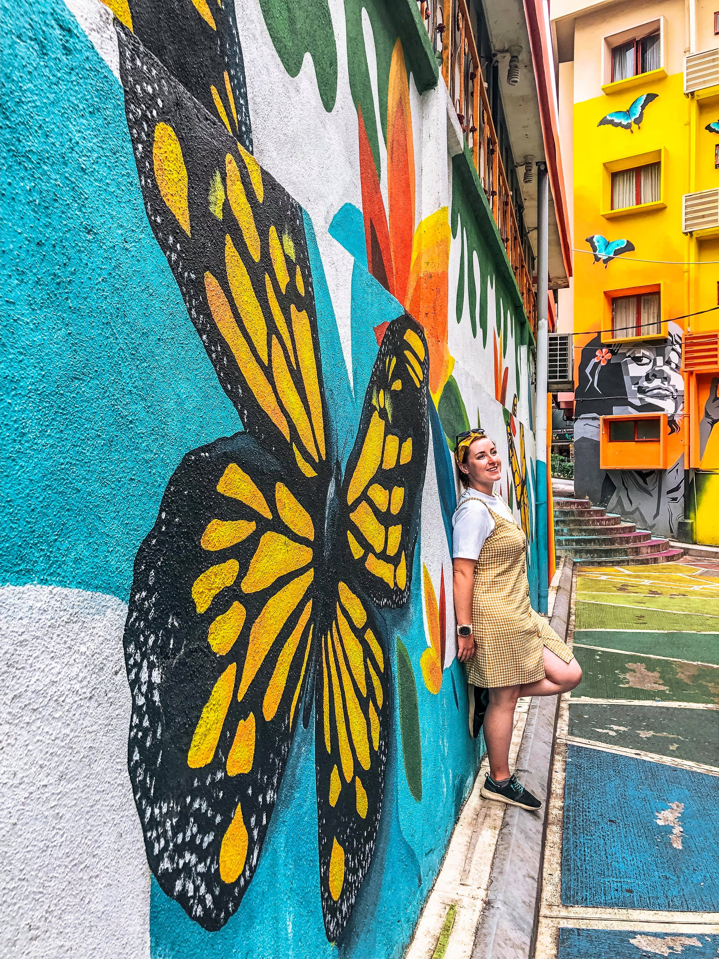 A girl leans against a wall with a giant butterfly on. Lots of rainbows and flower on the surrounding walls.