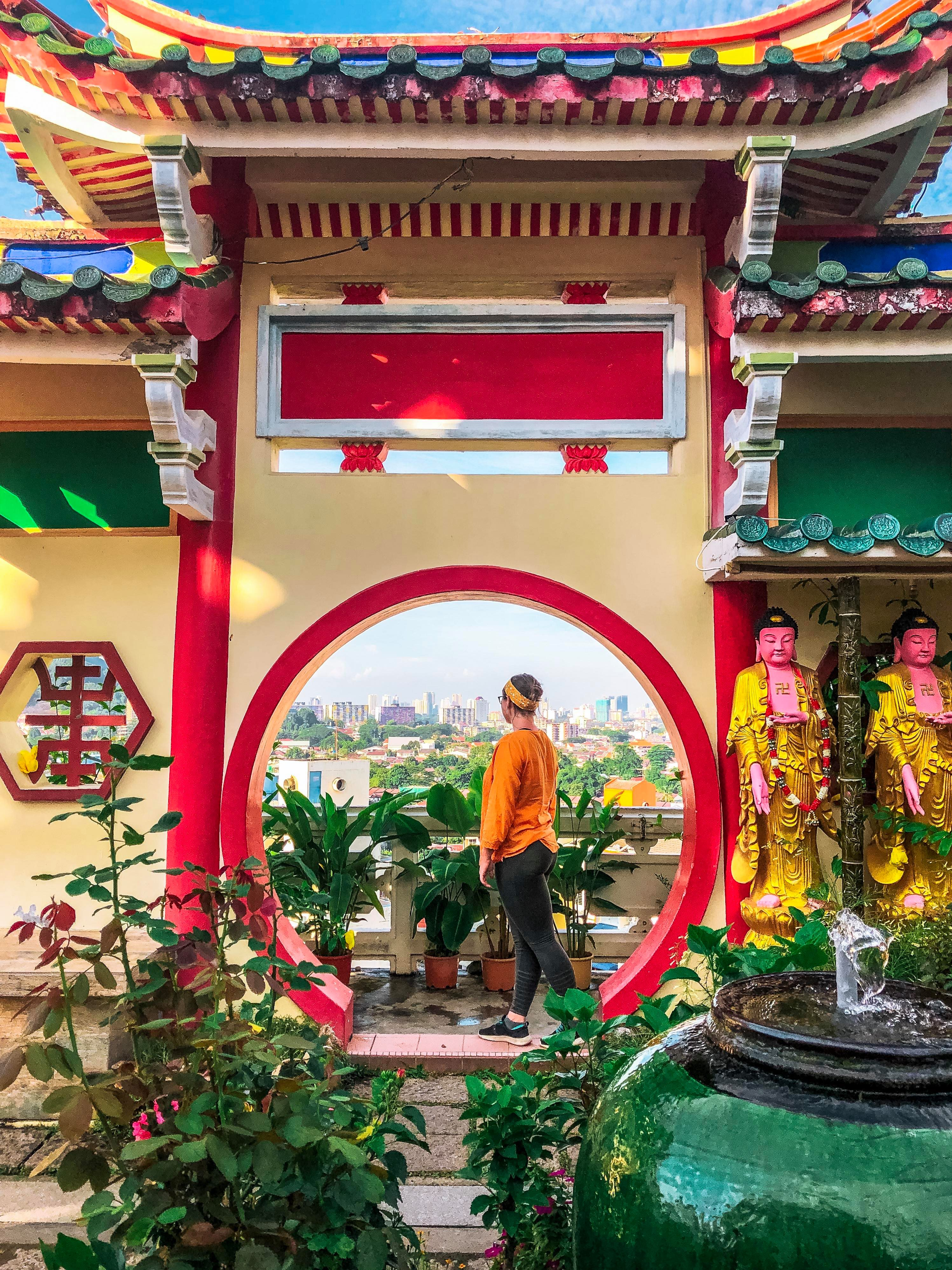 A girl looks over Georgetown in the middle of a red circle at a bright and colourful temple.