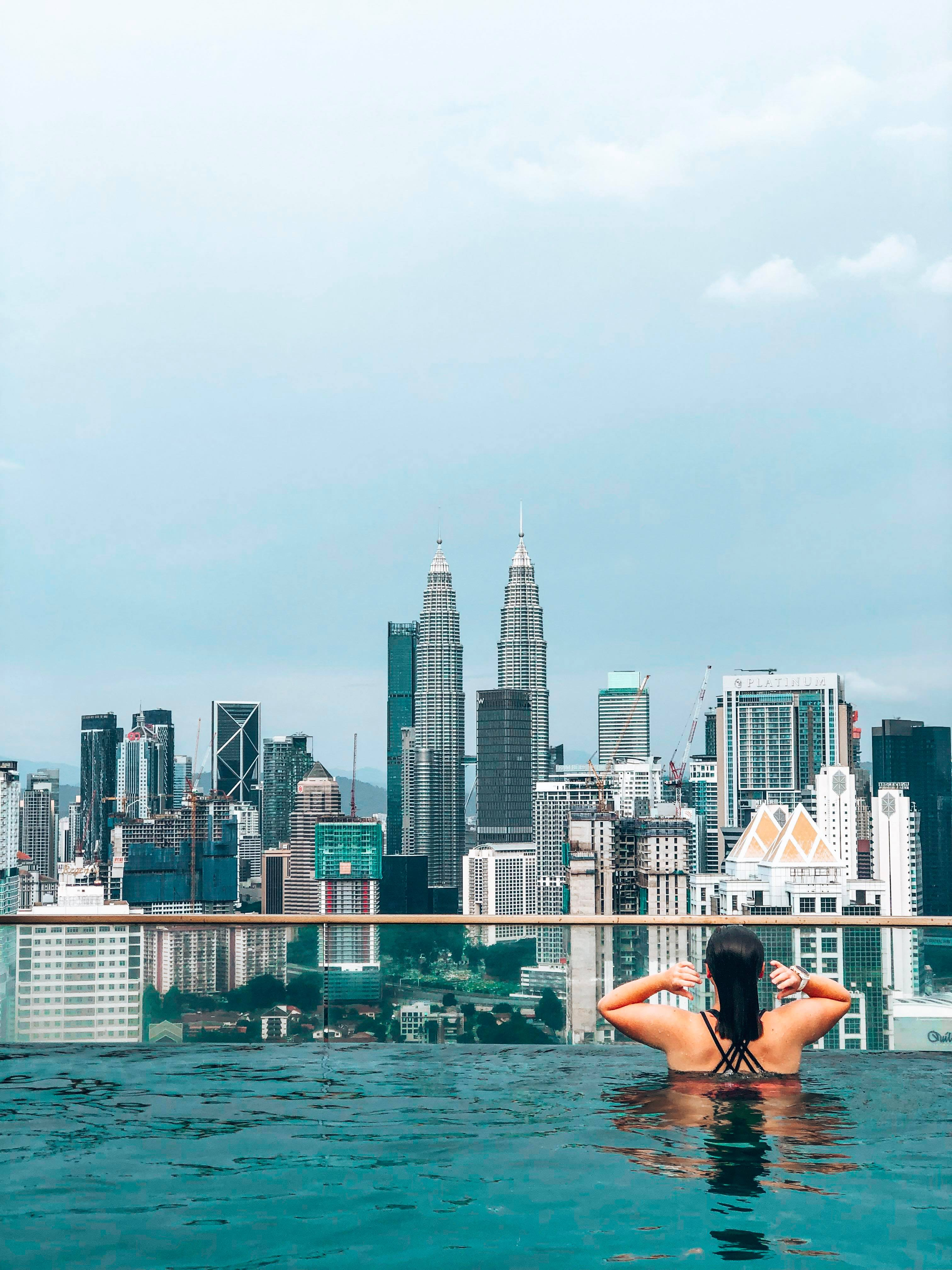 A girl in a pool looking over the Kuala lumpur sky line