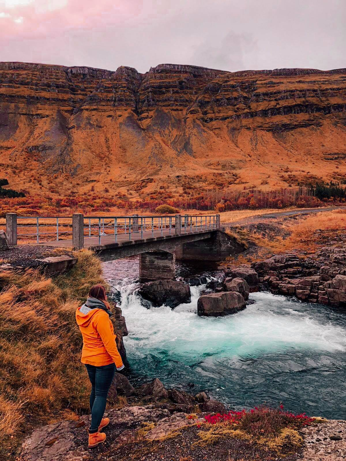 A girl in yellow jacket looking at a bridge on a bright blue river. The river is surrounded by orange and red grass/rocks.