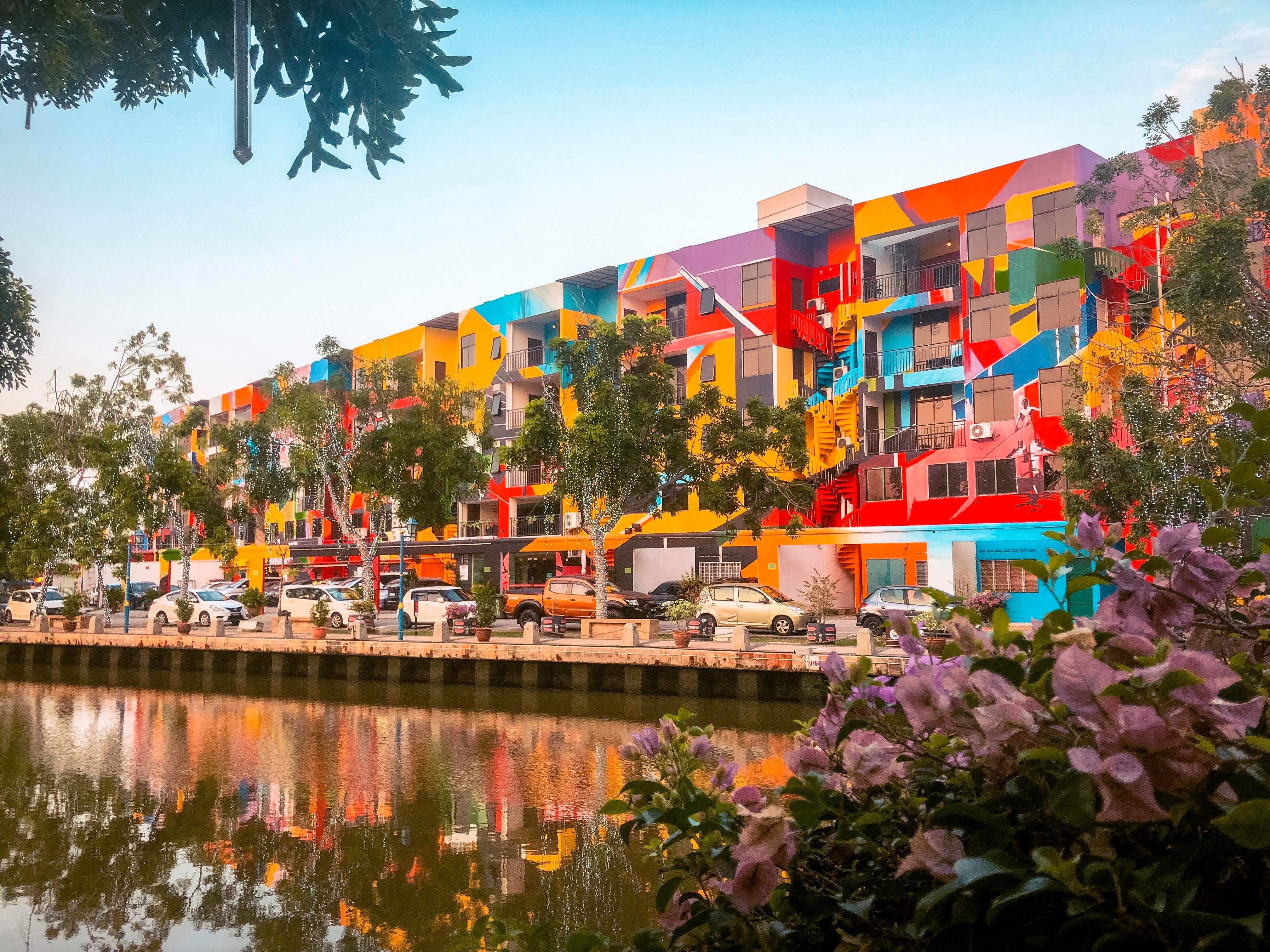 A building completely covered in rainbow colours and paint next to the river.