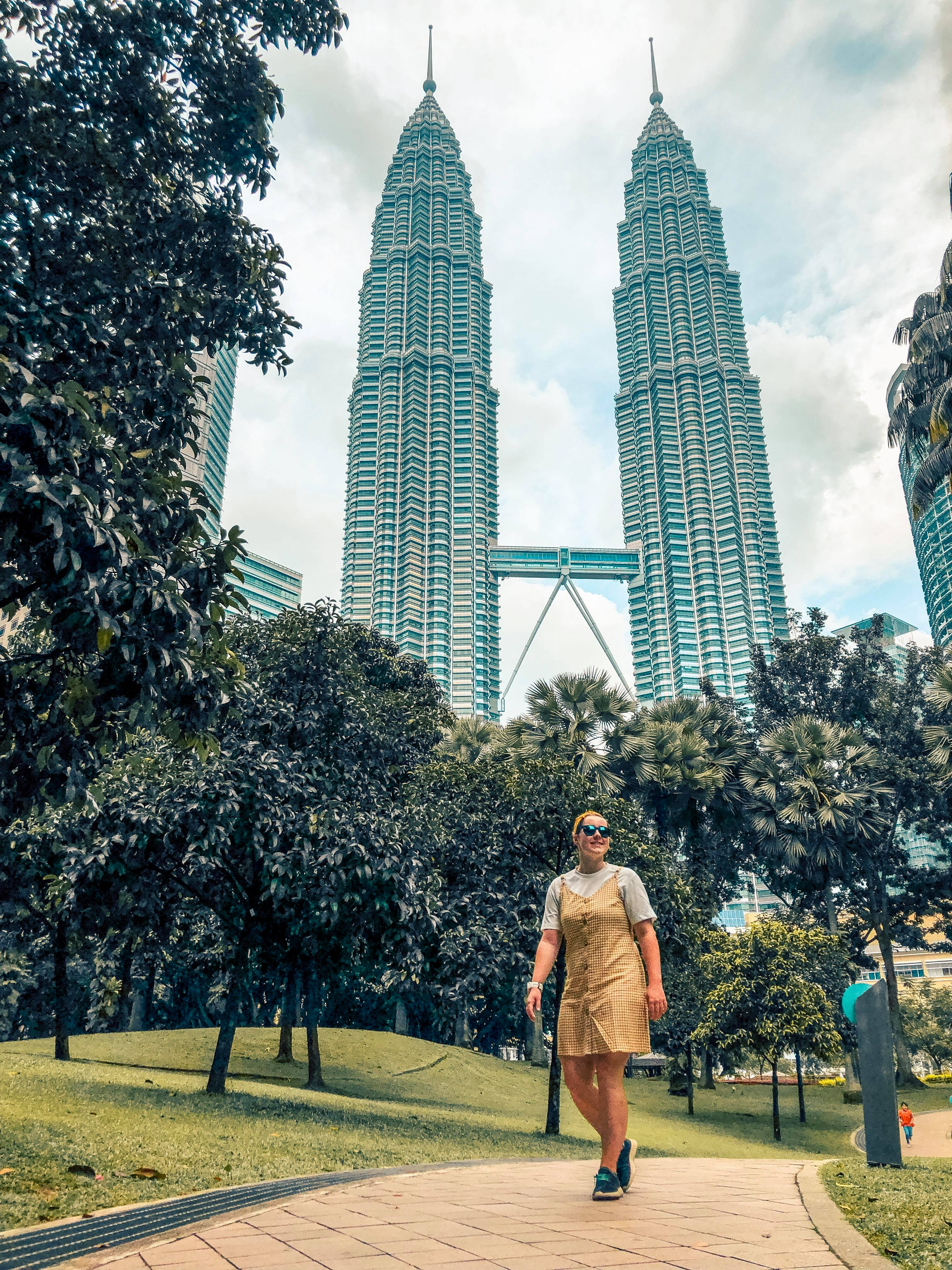 A girl in a yellow dress walking through a park with the KL two towers behind