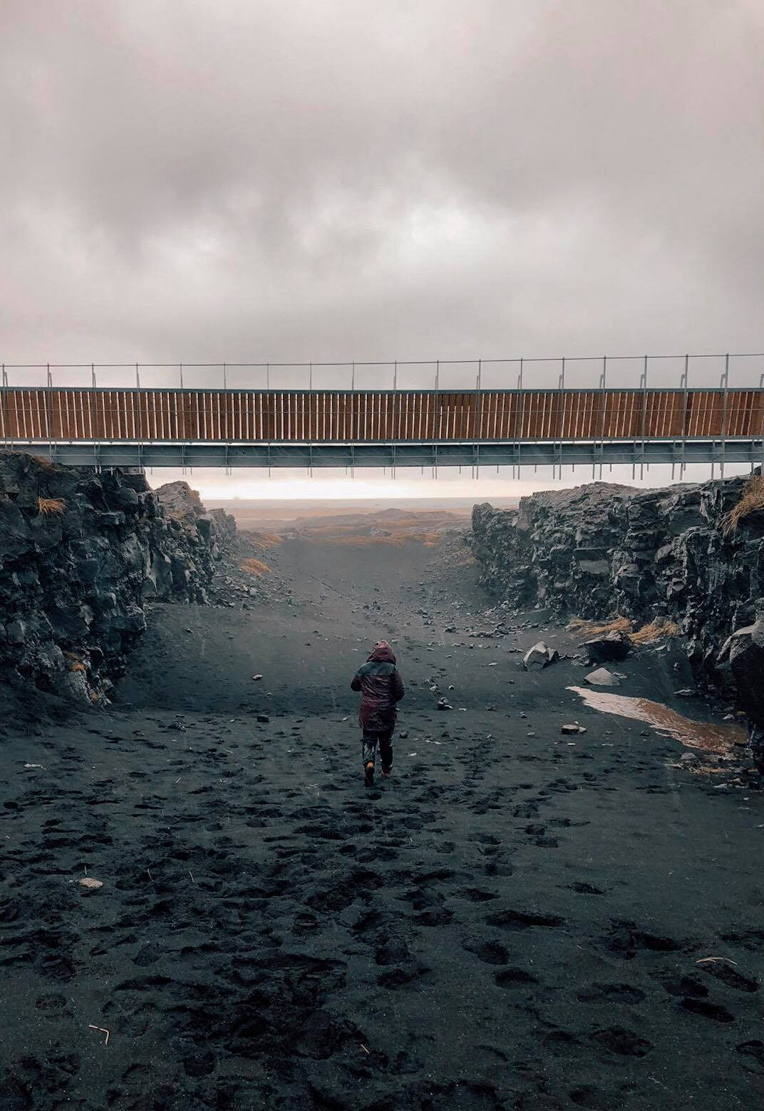 A girl running underneath the bridge across two continents. There is a lot of rain and footprints in the black sand below.