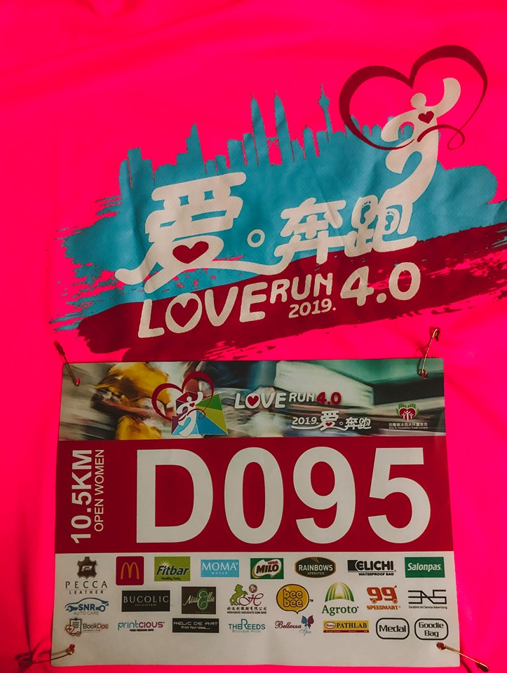 Running bib attached to the shirt you are provided for the race. The shirt is a bright pink colour with the logo on the front.