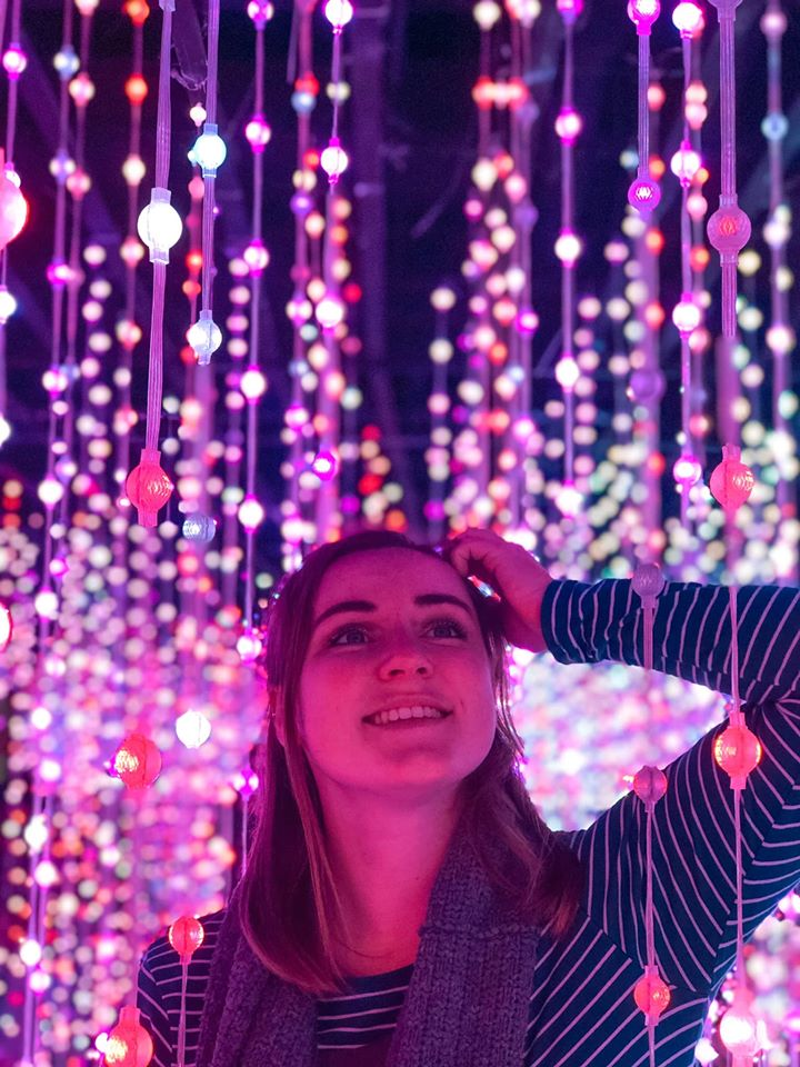 A girl with a pink shine in a field of infinity lights