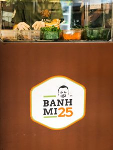 Banh Mi 25 logo and someone making the food