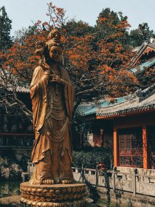 Golden statue surrounded by autumn leaves in the temple